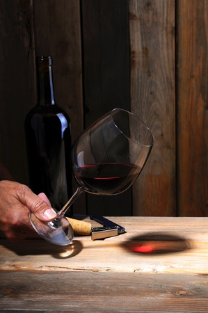 cabernet sauvignon: A winemaker holding a glass of wine to study its color in a wine cellar setting. Closeup on hand glass and bottle only.