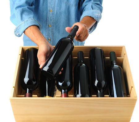 Winemaker standing behind a case of red wine holding one bottle in his hands over the open box. Square format over a white background photo
