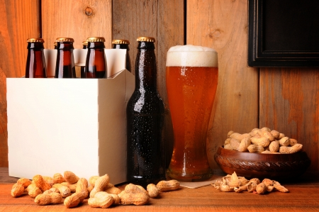 A glass of beer next to a six pack in a rustic tavern setting. Shelled peanuts in a bowl and strewn on the wood table surface. A blank picture frame in the upper right area ready for your type or image.