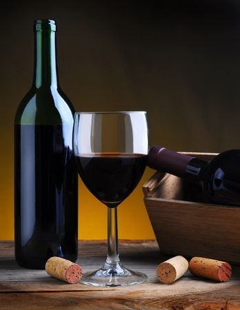 still life: Wine Glass and Wine Bottle on an old wood table with a warm background. Stock Photo