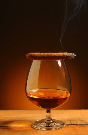 Brandy glass with a lit cigar on its rim over a warm background. Smoke trail wafting up from cigar. Glass is on rustic wood table. photo