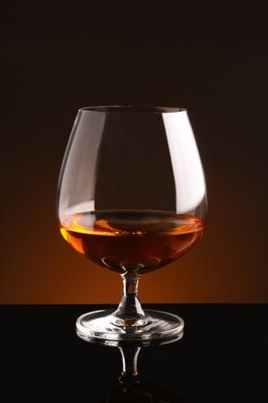 검은 반사 표면과 따뜻한 배경에 브랜디 유리.