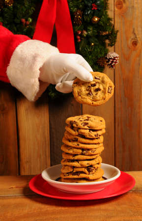 Santa Claus taking a chocolate chip cookie from large stack on plate.  photo