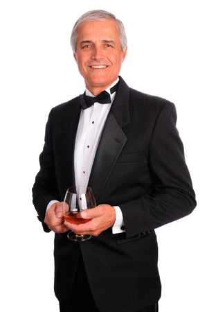 Smiling middle aged man wearing a tuxedo and holding a cognac glass. Vertical format isolated on white Foto de archivo