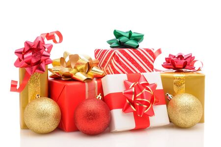 Group of wrapped christmas presents with tree ornaments on a  white background. Horizontal format with reflection.