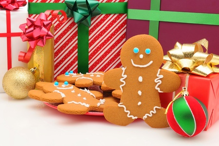 A plate of Ginger Bread Man cookies in front of Christmas presents. Horizontal format.