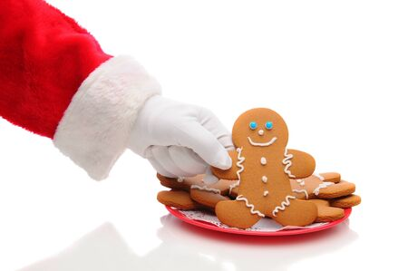 Santa Claus arm reaching to take a gingerbread man cookie from plate. Horizontal format over a white background with reflection - showing only hand and sleeve.. Stock Photo