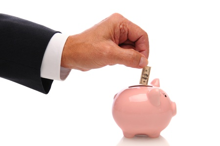 withdraw: A businessmans hand putting a small one hundred dollar bill into a piggy bank. Horizontal over a white background with reflection under bank. Stock Photo