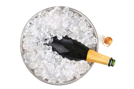 Overhead view of an open bottle of champagne in a metal ice bucket with condensation. Cork is on the  white background adjacent to the bottles neck.