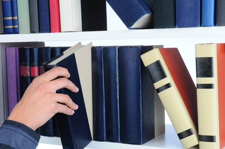 Closeup of a womans hand removing a book from a library shelf. photo