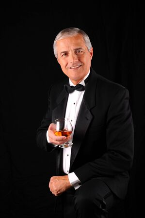 snifter: Middle aged man wearing a tuxedo and holding a brandy snifter. Man is smiling at the viewer, vertical format over a black bacvkground. Stock Photo
