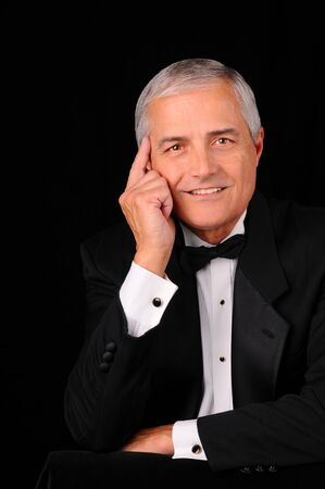 Portrait of a middle aged man in a tuxedo over a black background.