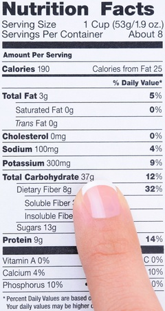 Closeup of a womans finger pointing at a food product nutrition label.