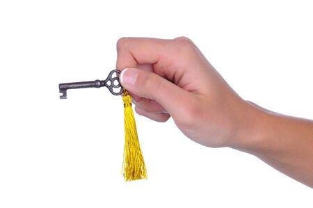 白い背景の上の黄金のタッセルに古い昔ながらキーを持つ女の手