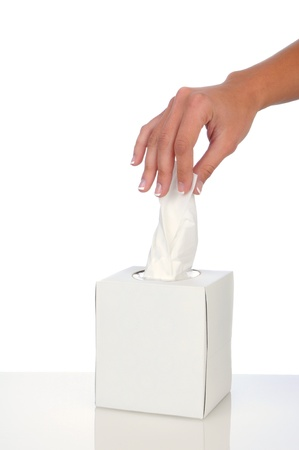 facial tissue: Closeup of a womans hand pulling a facial tissue from a box. Vertical format over a white background.