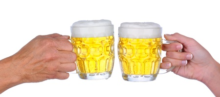 Closeup of a male and female hand a woman hand holding a beer mug  with a frothy head about to clink glasses, over a white background. Stock Photo - 11990242