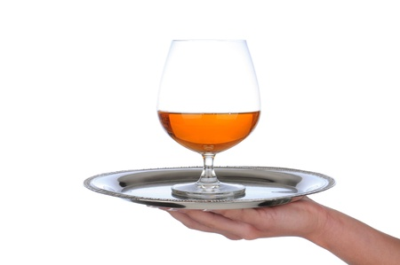 serving tray: Closeup of a brandy snifter on a silver serving tray held by a womans hand, Horizontal format over a white background.