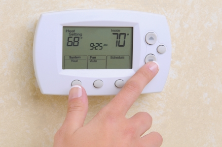 temperature: Closeup of a womans hand setting the room temperature on a modern programmable thermostat.