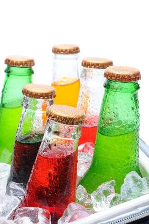 ice chest: Closeup of six assorted soda bottles in an ice cooler with condensation. Vertical format over white with shallow depth of field.