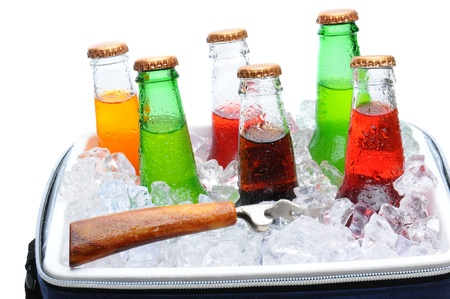cooler: Assorted soda bottles in a cooler full of ice with bottle opener. Horizontal format over white.