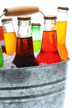 soda bottle: Closeup of assorted soda bottles in a metal bucket full of ice. Vertical format over white.