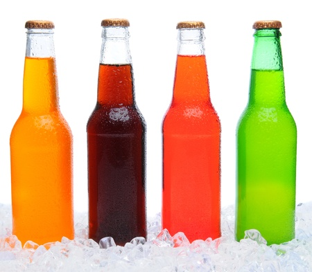 soft drinks: Closeup of four assorted soda bottles standing in ice with condensation. Horizontal format over a white background.