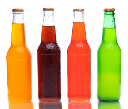 root beer: Four assorted soda bottles on white with reflection.