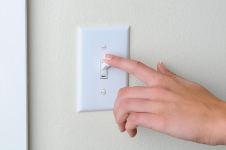 Womans hand with finger on light switch, about to turn off the lights. Closeup of hand and switch only. Horizontal format. photo