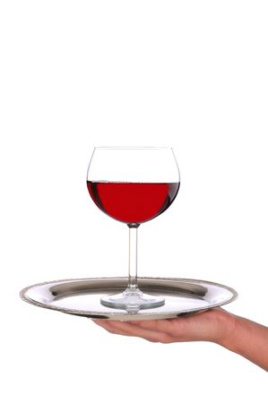 alcohol server: Waitresses hand and arm holding a silver serving tray with a glass of red wine. Vertical format over a white background.
