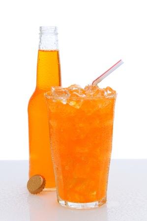 carbonation: Una copa fr�a de refresco de naranja con hielo y una pajita para beber, con una botella escondido detr�s. El contador a est� h�meda y una tapa de botella se apoya contra la botella. Formato vertical con un fondo blanco Foto de archivo