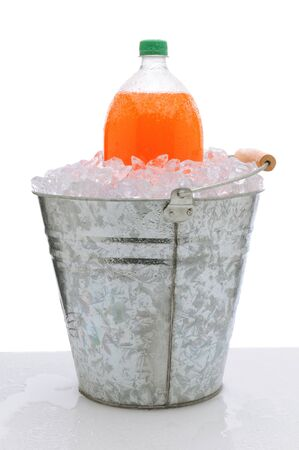 An orange two liter soda bottle in a metal bucket full of ice on a wet countertop. Vertical format over a white background. photo