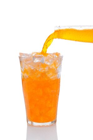 carbonated: Closeup of a bottle of Orange Soda Pouring into Glass of Ice. Vertical format over a white background with reflection.