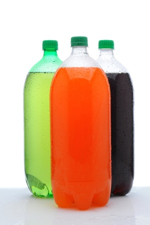 soda: Three plastic two liter soda bottles with condensation on a wet counter. Vertical format over a white background.
