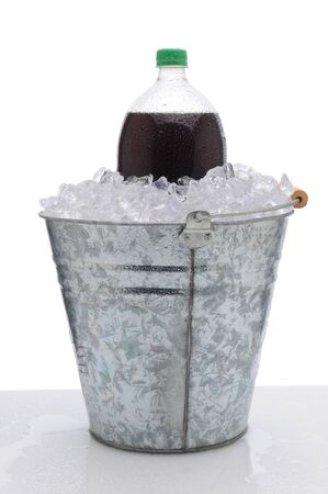 A two liter cola soda bottle in a metal bucket full of ice on a wet countertop. Vertical format over a white background. photo