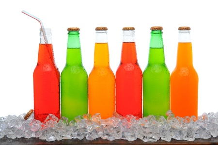 flavoured: A line of assorted soda bottles standing in a field of ice cubes on a wooden table. Horizontal format with a white background.