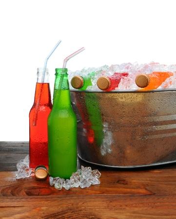 carbonation: Un cubo de metal en las partes de una tabla de madera llena de refresco fr�o. Dos botellas en la mesa con pajitas para beber. Foto de archivo
