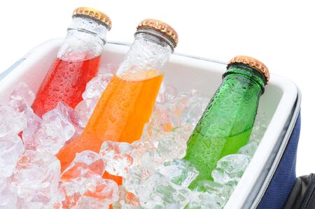 ice chest: Closeup of three different soda bottles in a small cooler full of ice cubes. Stock Photo