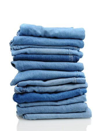 folded clothes: A stack of denim blue jeans over white with reflection. Stock Photo
