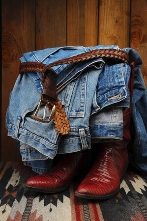 Denim blue jeans tied with a leather belt draped over a pair of cowboy boots in a rustic western setting. photo