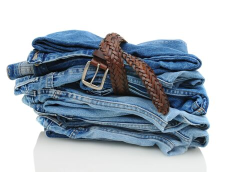 A stack of denim blue jeans over white with reflection. Horizontal format with some pants tied up with a belt. Banco de Imagens