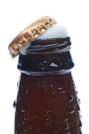 Closeup of a beer bottle top with the cap askew and foam bubbling up. Vertical format over a white background. photo