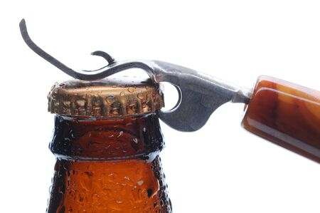 pry: Macro shot of a brown beer bottle with an opener ready to pry up the bottle cap. Horizontal format over white.