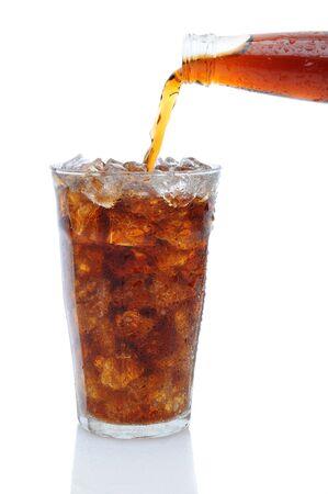 carbonation: Una botella de refresco de cola se vierte en un vaso lleno de cubitos de hielo sobre un fondo blanco con la reflexi�n.