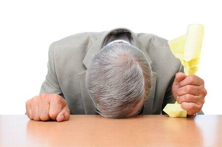 A frustrated businessman with his head on his desk and a piece of crumpled paper in one hand.  Stock Photo - 12596744