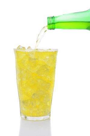 lima limon: Una botella de refresco de lima lim�n se vierte en un vaso lleno de cubitos de hielo sobre un fondo blanco. Foto de archivo