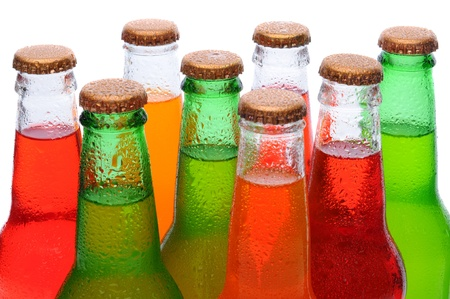 Closeup of several assorted flavors of soda pop. Orange, lemon lime, and strawberry soda bottles necks only over a white background. photo