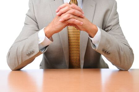 clasped: Closeup of a businessman seated with his elbows on his desk with hands clasped together. Horizontal format over white, man is unrecognizable. Stock Photo