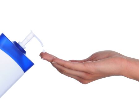 salve: Closeup of a womans hand and lotion bottle with a drop of cream on one finger. Horizontal format over a white background. Stock Photo