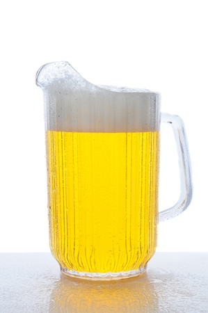 Pitcher of beer on a wet bar counter top. Vertical format over white.
