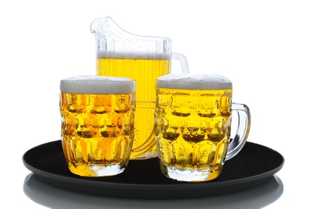 A pitcher of beer and two full glasses on a serving tray over a white background. Stock Photo - 12853737
